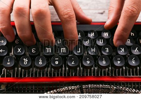 Vintage red typewriter on the table with hands on wark