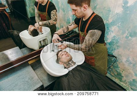 Man Getting Trendy Haircut At Barber Shop. Male Hairstylist In Tattoos Serving Client, Washing Head