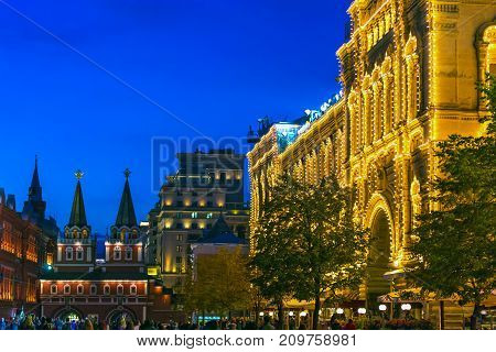 The building is decorated with Christmas lighting trees and people walk. In the distance the Resurrection Gate of China-city. Evening blue sky. Facade of GUM, Red Square, Moscow, Russia.