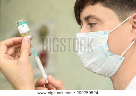 Male cosmetologist with medical mask on face