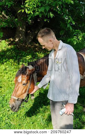 Man is standing next to a horse and stroking his head.