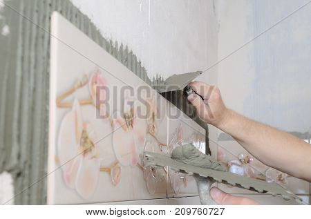 Tilers hands are putting on a tile adhesive on the wall in the bathroom.