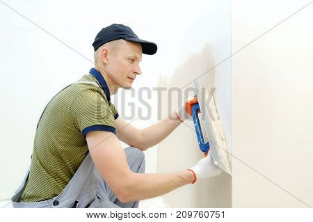 A worker is plastering a wall in a apartment with a long trowel.