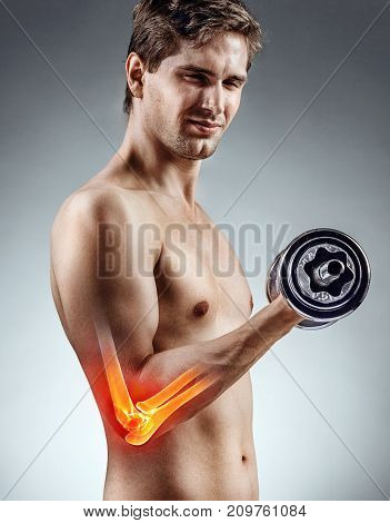 Man holding a dumbbell. Photo of young man highlighting a sportsperson's injury. Medical concept.
