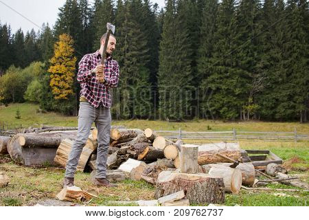 yong male in forest choping wood with steel axe, country landscape with lumberjack