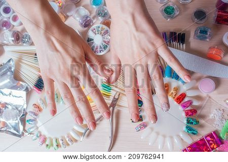 The female hand uses the decor to cover the nails with gel