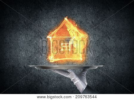 Cropped image of waitress's hand in white glove presenting flaming house symbol on metal tray with dark wall on background.