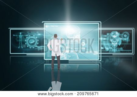 Handsome doctor pointing against 3D screens with blue interface