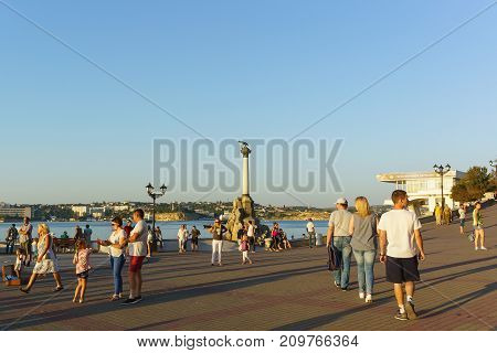 Russia Crimea Sevastopol - September 03.2017: Tourists on quay of the black sea city near the Monument to the scuttled ships