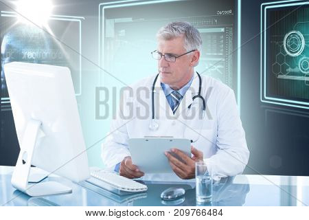 Male doctor holding clipboard while looking at computer monitor against composite 3D image of different application interface