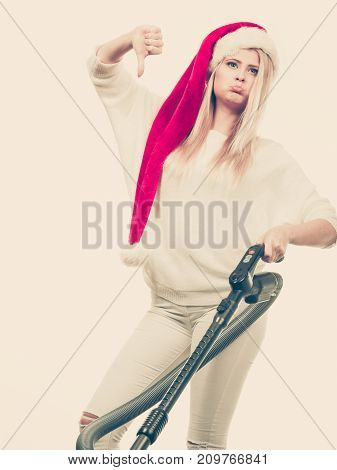 Sad Girl In Santa Helper Hat With Vacuum Cleaner