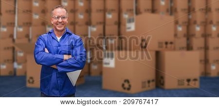 Smiling warehouse manager standing with arms crossed against closed door of warehouse