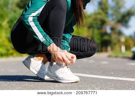 Photo athletic girl ties up shoelaces on sneakers