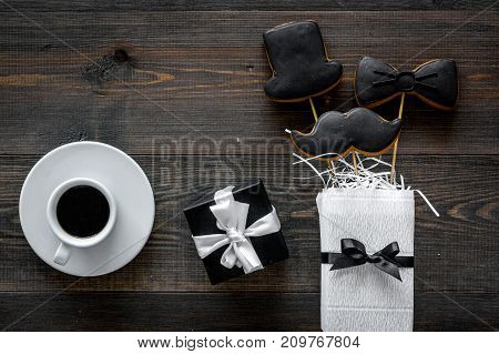 Father's day or birthday celebration with present, black tie, mustache and hat sign cookies on dark wooden desk background flat lay copyspace