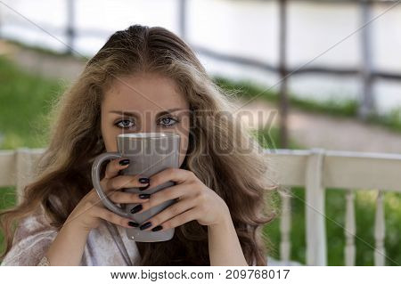 Portrait of young woman with beautiful eyes and long thick hair holding a large cup in front of her face. Relaxing morning outdoors. Green nature background. Close shot.