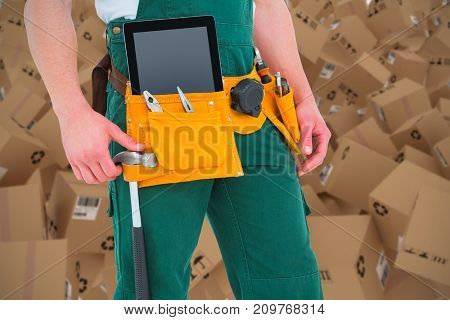 Construction worker wearing tools belt against 3D cardboard boxes in warehouse