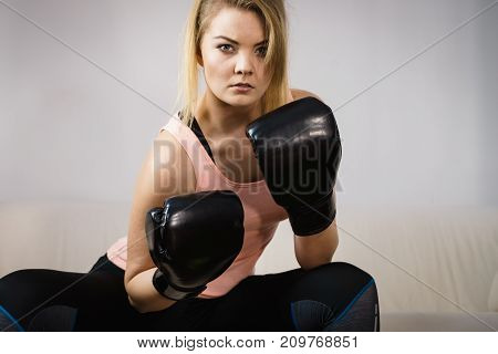 Sporty woman wearing red boxing gloves fighting.