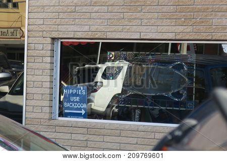 Store window with joke sign in it.