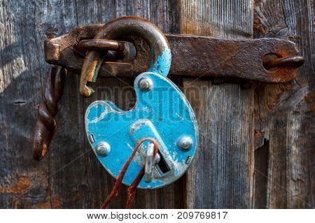 Padlock on the garage door. Gate locked on the castle. Vintage old.Door hinges. closed. Storage room garage hangar.open lock door breaking