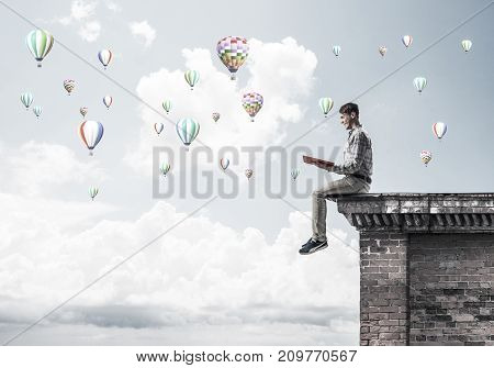 Young shocked man or student sitting on building top with red book in hands