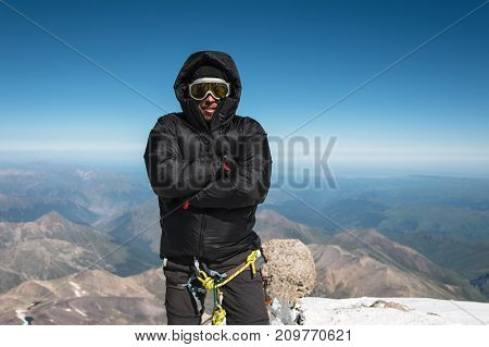Climber on the summit. An equipped mountaineer in a ski mask and down jacket with a hood that is cold on top of the mountain. The concept of relaxation in the mountains