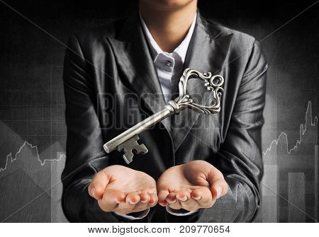 Cropped image of businessman in suit keeping big key in hands with business sketches on dark wall on background.