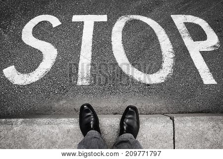 Feet of a man in black shining shoes standing opposite stop road marking