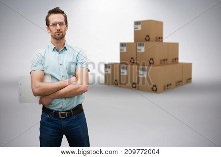 Composite 3D image of serious warehouse manager standing with arms crossed against grey background