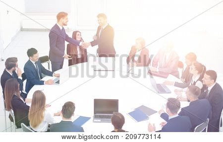 smiling business partners shaking hands at a business meeting to