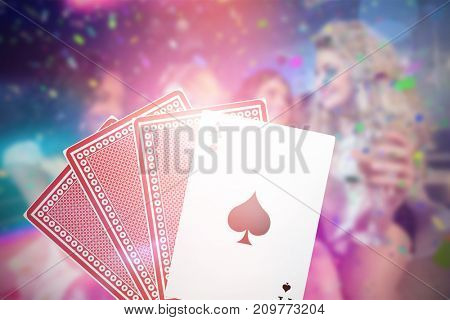 Pretty girls holding champagne 3D glass against ace of spades with playing cards