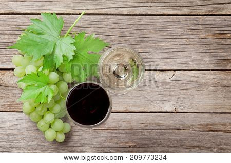 Wine glasses and grapes on wooden table. Top view with space for your text