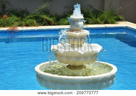 A multi-tiered fountain in a blue pool