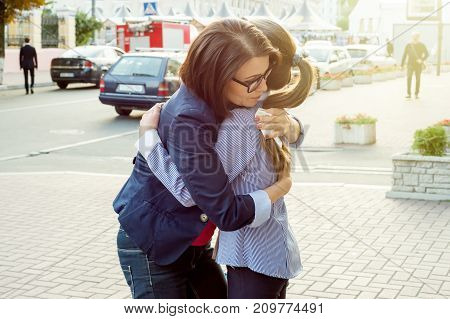 Mother consoling her crying daughter standing in front of a fire engine.