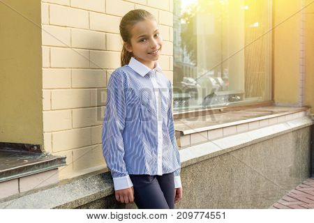 Portrait of a girl of 10-11 years old. Urban background