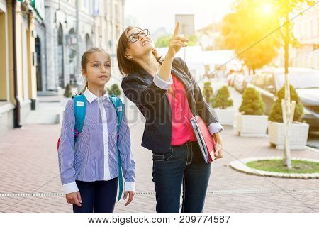 Outdoor portrait of a schoolgirl and her teacher.