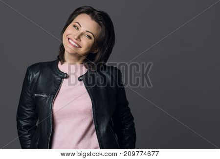 Close-up Shot Of A Beautiful Mid Adult Woman  Smiling On Grey Background.