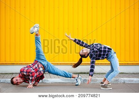 portrait of carefree young couple dancing holding hands in street and enjoying life