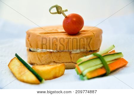Burger with cherry tomato, sliced potatoes and chopped vegetables. Hamburger and vegetables slices on a napkin. Beefburger. Healthy and unhealthy fast food.