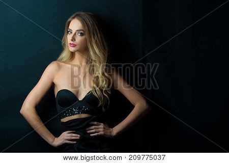 young beautiful sensual girl with makeup and hairdress on a black background