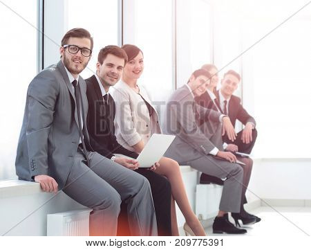 business team sitting on the windowsill in the new office