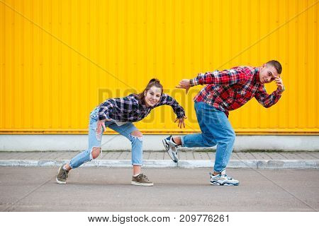 Photo of carefree young couple that dancing on street and smiling