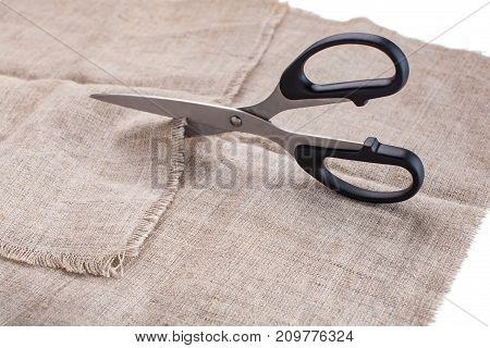 The Tailor's Scissors Cut Linen Fabric On A White Background.