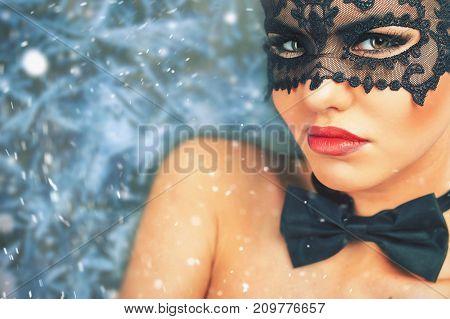 Beautiful woman with carnival mask looking at camera, christmas night. Cristmas party. Secret. Fashion. Venetian carnival. Hot babe.