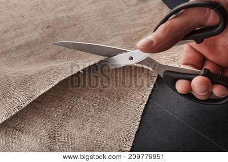 A Man's Hand Cuts Linen Cloth With Tailor's Scissors.