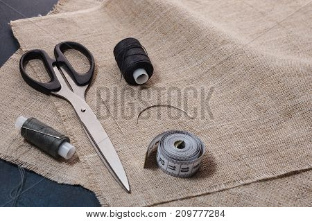 Sewing Accessories On A Background Of Canvas Fabric.