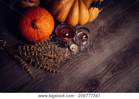 a composition for decorating a house for halloween, on a wooden floor lie yellow and orangent pumpkins, burning scented candles