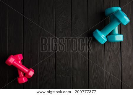 Small pink and big blue dumbbells for sports exercises. Sports equipment on a dark gray wooden parquet. Close-up of dumbbells. Sport concept.