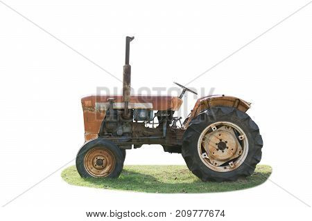 Old rusty tractor on grass green isolated on white
