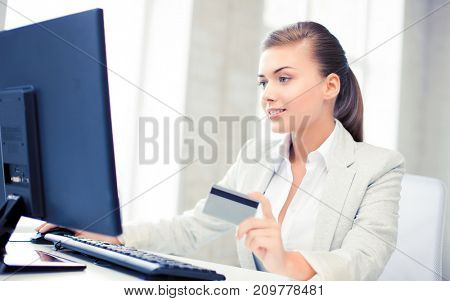 smiling businesswoman with computer using credit card