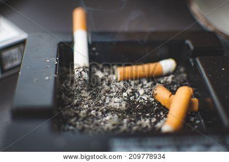 Blurred cigarette, smoke, ashtray and ash background